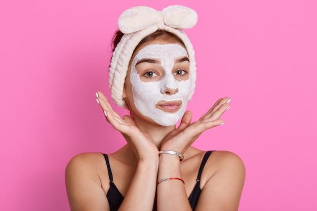 A mulher adorável tem um olhar feliz, mantém as mãos sob o queixo, hidrata e acalma a pele, usa uma faixa de cabelo de nádegas com laço na cabeça.