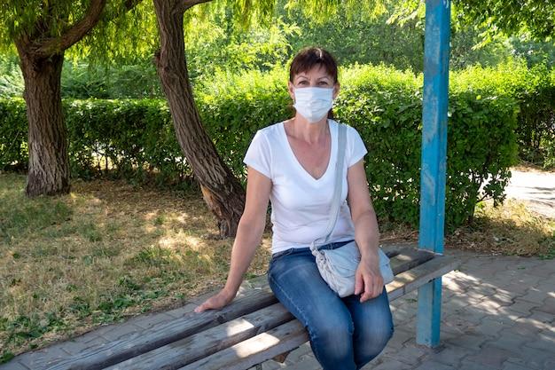 A mulher adulta em máscara protetora senta-se sozinha no ponto de ônibus vazio e aguarda o transporte público. distância social
