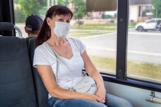 A mulher adulta em uma máscara protetora monta sozinha em um transporte público vazio