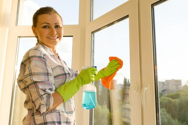 A mulher adulta lava janelas, limpando a casa.