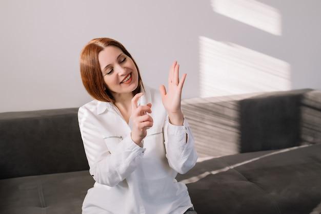 A mulher adulta limpa as mãos com um spray para lavagem das mãos à base de álcool como medida preventiva de higiene contra a infecção por coronavírus (sars-cov-2, covid-19). gel antibacteriano desinfetante para as mãos.