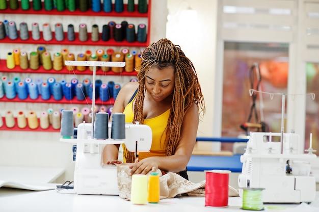 A mulher africana nova da costureira costura a roupa na máquina de costura no escritório do alfaiate. mulheres de costureira negra.