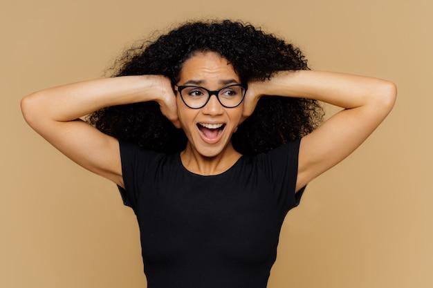 A mulher afro-americana emocional cobre os ouvidos, grita alto, não aguento barulho, as demandas desligam a música