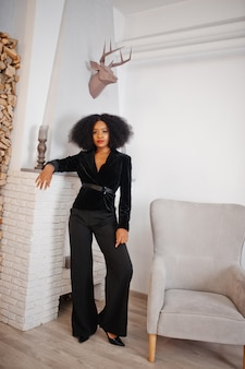 A mulher afro-americano à moda no preto levantou na sala contra o lugar do fogo.