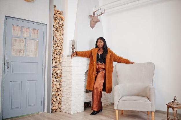 A mulher afro-americano à moda no revestimento alaranjado levantou na sala contra a lareira.