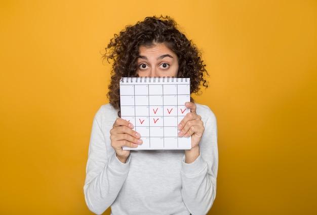 A mulher afro-americano bonita guarda marcas os dias da menstruação no período de calendário.