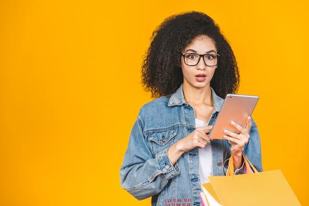 A mulher afro-americano bonita nova de sportrait chocou com os sacos de compras e o tablet pc coloridos isolados sobre o fundo amarelo.