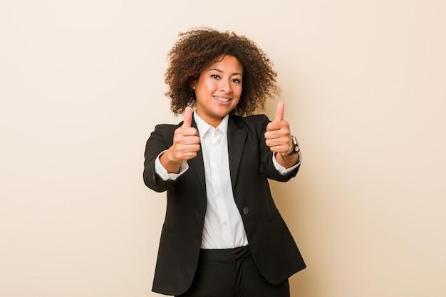 A mulher afro-americano do negócio novo com polegares levanta, felicidades sobre algo, apoia e respeita o conceito.