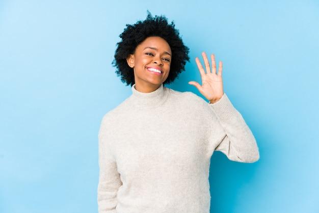 A mulher afro-americano envelhecida meio contra uma parede azul isolou mostrar alegre número cinco de sorriso com dedos.