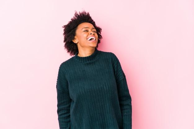 A mulher afro-americano envelhecida meio contra uma parede cor-de-rosa isolou o riso relaxado e feliz, pescoço esticado mostrando os dentes.