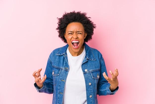 A mulher afro-americano nova contra um backgroound cor-de-rosa isolou gritar com raiva.