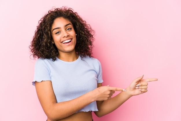 A mulher afro-americano nova contra uma parede cor-de-rosa excitou apontar com os dedos indicadores afastado.