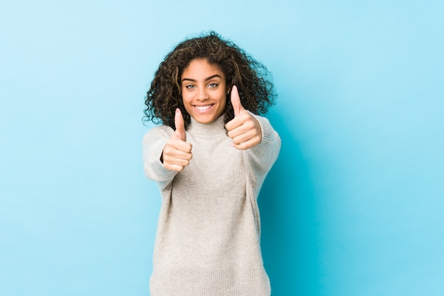 A mulher afro-americano nova do cabelo encaracolado com polegares levanta, felicidades sobre algo, apoia e respeita o conceito.