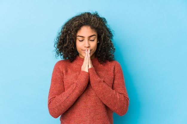 A mulher afro-americano nova do cabelo encaracolado que guarda as mãos reza perto da boca, sente-se confiante.