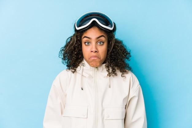 A mulher afro-americano nova do esquiador isolada encolhe os ombros e abre os olhos confusos.