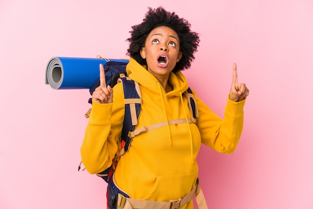 A mulher afro-americano nova do mochileiro isolou apontar a cabeça com boca aberta.