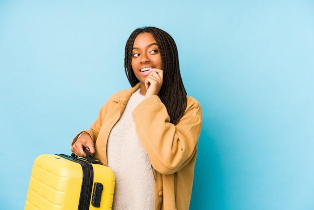 A mulher afro-americano nova do viajante que guarda uma mala de viagem isolou o pensamento relaxado sobre algo que olha um espaço da cópia.