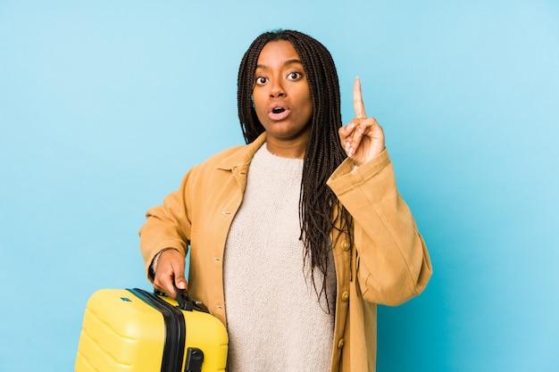 A mulher afro-americano nova do viajante que mantem uma mala de viagem isolada tendo alguma grande ideia, conceito da faculdade criadora.