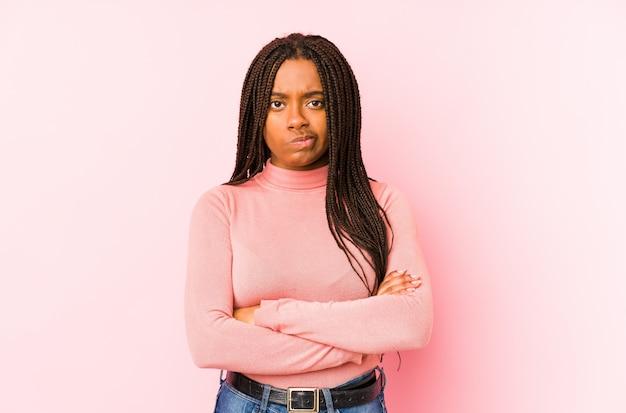 A mulher afro-americano nova isolada em uma cara carrancuda do fundo cor-de-rosa no descontentamento, mantém os braços dobrados.