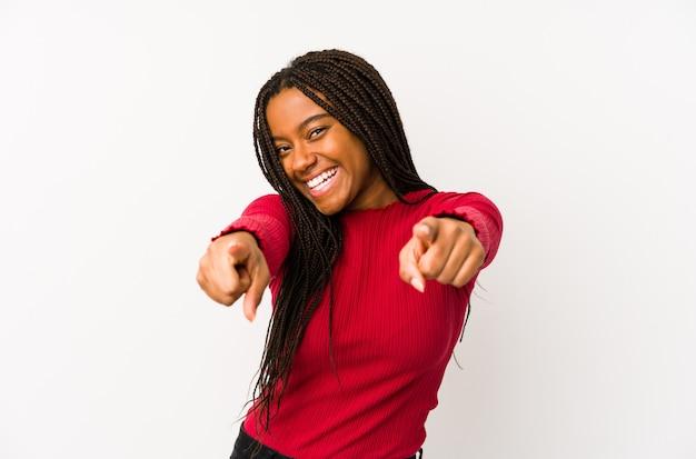A mulher afro-americano nova isolou os sorrisos alegres que apontam para a parte dianteira.