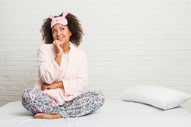 A mulher afro-americano nova na cama que veste o pijama relaxou o pensamento sobre algo que olha um espaço da cópia.