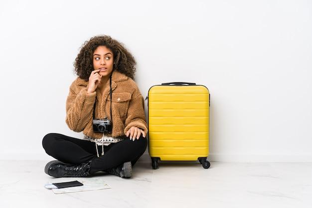 A mulher afro-americano nova pronta para uma viagem relaxou o pensamento sobre algo que olha um espaço da cópia.