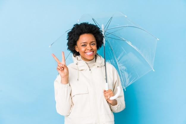 A mulher afro-americano nova que guarda um guarda-chuva isolou mostrar o número dois com dedos.