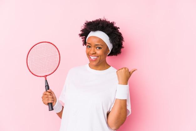 A mulher afro-americano nova que joga o badminton isolou pontos com o dedo do polegar afastado, rindo e despreocupado.