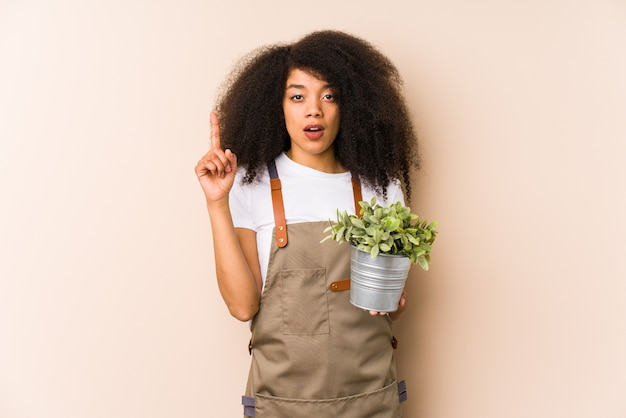 A mulher afro nova do jardineiro que guarda uma planta isolatedhaving alguma grande ideia, conceito da faculdade criadora.