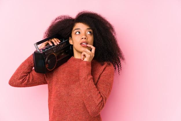 A mulher afro nova que guarda um cassete isolou o pensamento relaxado sobre algo que olha um espaço da cópia.