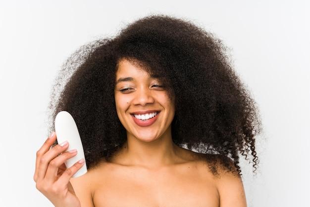 A mulher afro nova que guarda um creme hidratante isolou o sorriso seguro com braços cruzados.