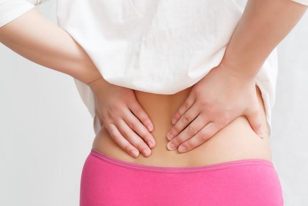 A mulher agarrou sua cintura com as duas mãos. o conceito de dor lombar