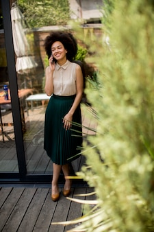 A mulher alegre do cabelo encaracolado usa um telefone dentro ao estar no pátio