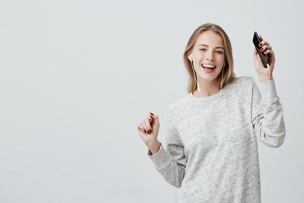 A mulher alegre feliz de sorriso dança, prende o telefone móvel, contente de receber a mensagem