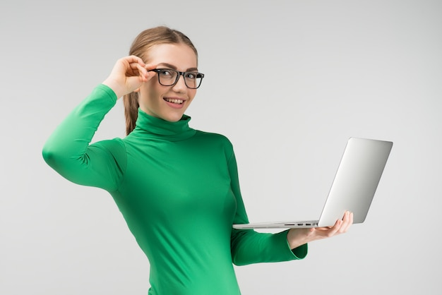A mulher alegre nos vidros trabalha em um portátil que guarda o em suas mãos ao estar contra no fundo branco. olha para a câmera