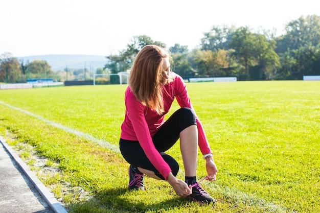 A mulher amarrando seus cadarços antes de começar o treino
