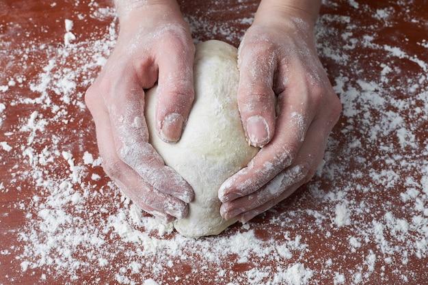 A mulher amassa a massa com as mãos. mãos femininas e massa crua