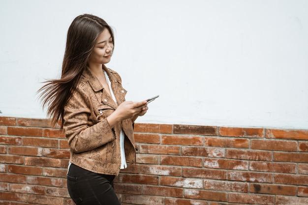 A mulher anda enquanto texting em seu telefone móvel