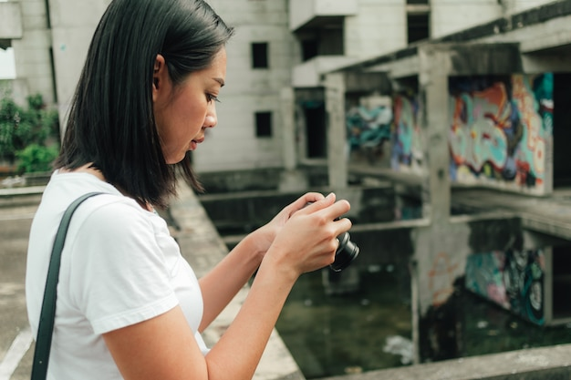 A mulher aprecia a tomada da foto de um edifício abandonado desconhecido.