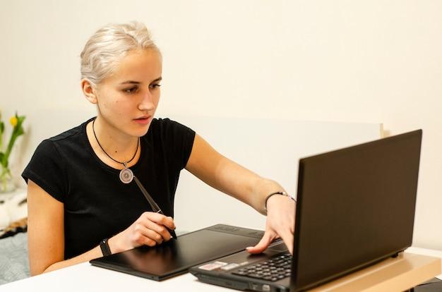 A mulher aprende a desenhar em uma mesa digitalizadora