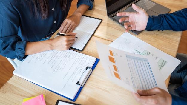 A mulher aprende e ensina a educação do conceito do tutor que ajuda-se sentado em uma tabela na sala de aula.