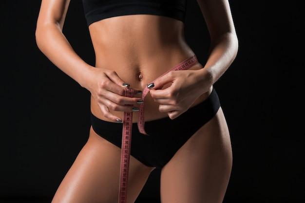 A mulher apta medindo a forma perfeita de uma bela figura. estilos de vida saudáveis e conceito de fitness