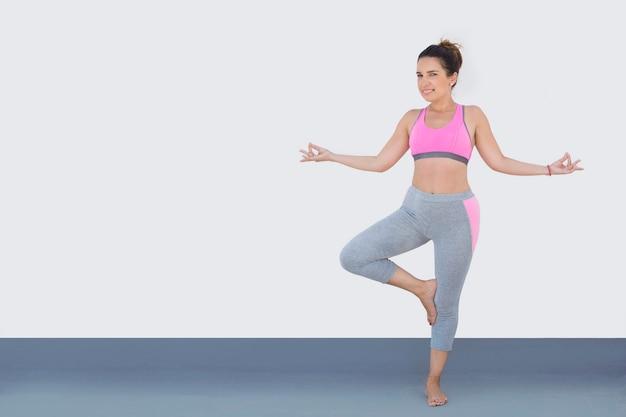 A mulher apta vestida para o esporte na postura da ioga, isolada no branco.