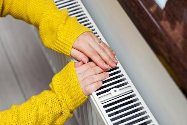 A mulher aquece as mãos no radiador