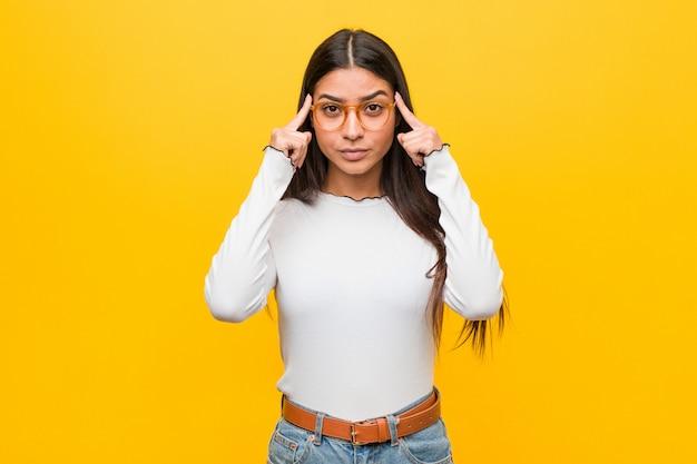 A mulher árabe bonita nova contra um amarelo focalizou em uma tarefa, mantendo os dedos apontando a cabeça.