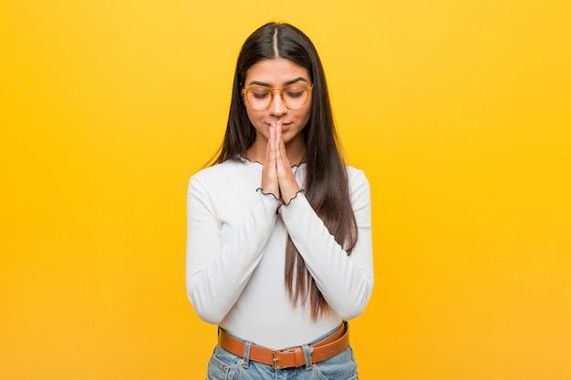 A mulher árabe bonita nova contra uma parede amarela que guarda as mãos reza perto da boca, sente-se confiante.