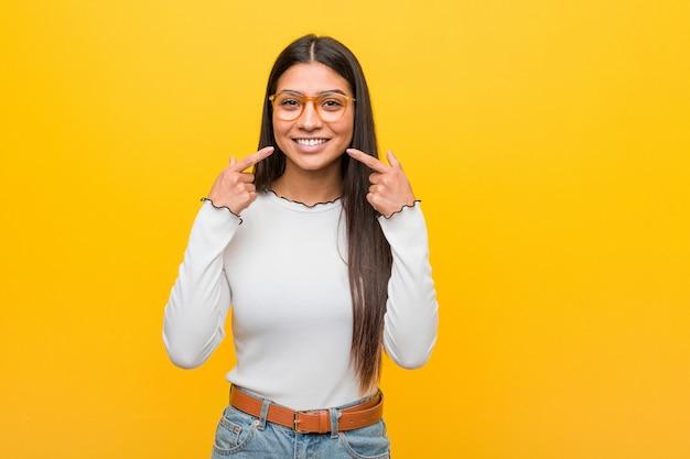 A mulher árabe bonita nova contra uma parede amarela sorri, apontando os dedos na boca.