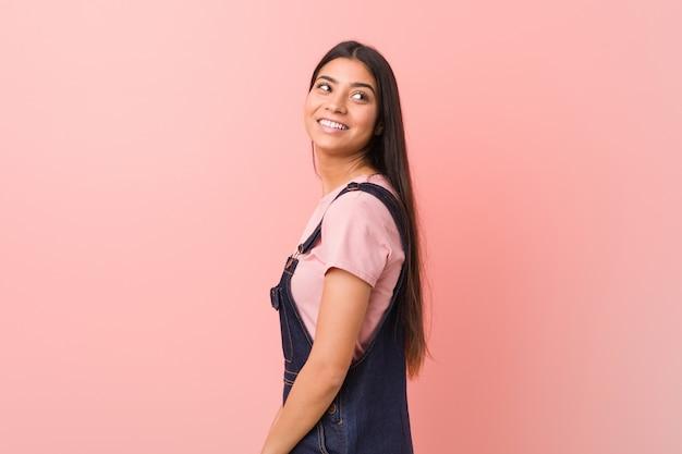 A mulher árabe bonita nova que veste um dungaree das calças de brim olha de lado o sorriso, alegre e agradável.