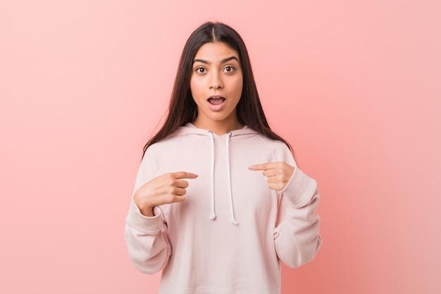 A mulher árabe bonita nova que veste um olhar ocasional do esporte surpreendeu apontar com o dedo, sorrindo amplamente.