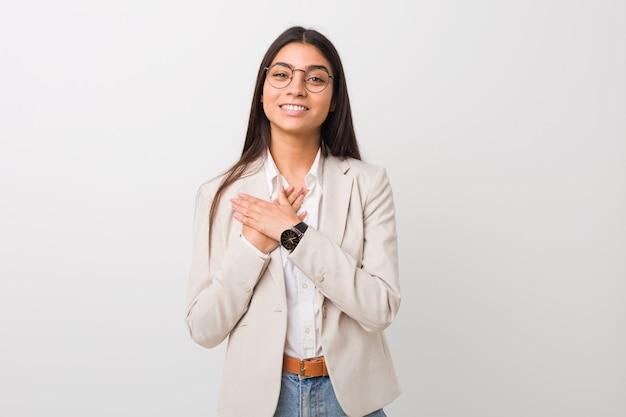 A mulher árabe de negócios jovem isolada contra uma parede branca tem expressão amigável, pressionando a palma da mão no peito. conceito de amor